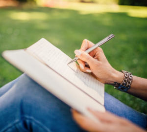 write better after doing podcasting - image of a woman's hands writing in a journal